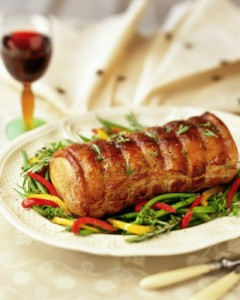 Roasted pork loin, served in plate with peppers and beans